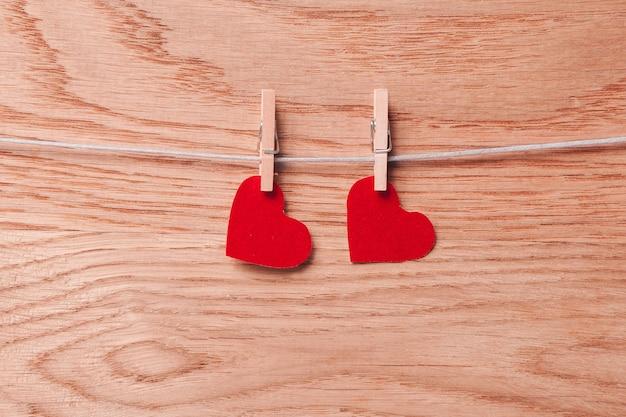 Linha de corações de papel vermelho em prendedores de roupa em fundo de madeira.
