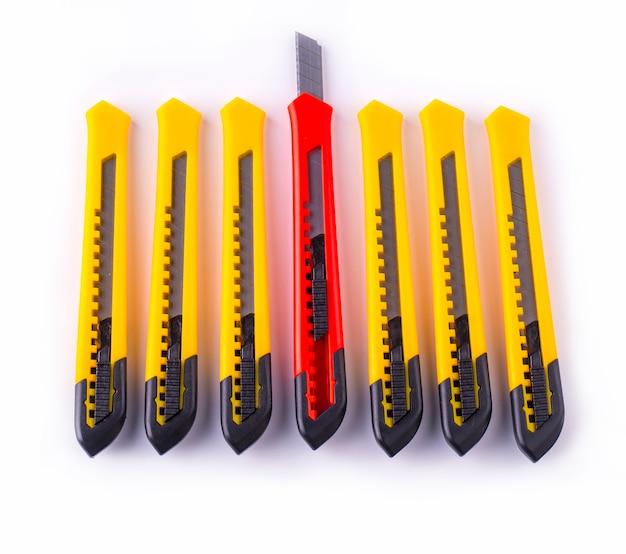 Linha de cortadores de papel amarelo e vermelho com lâmina fechada e aberta, isolada