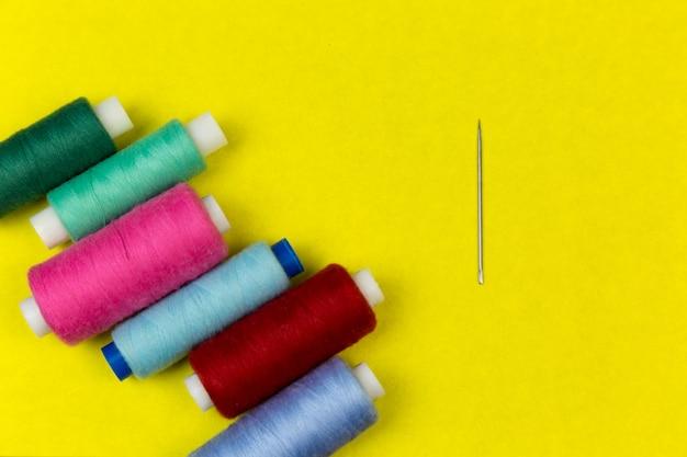 Linha de costura e agulha sobre um fundo amarelo.