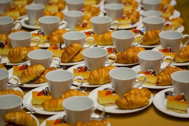 Linha de croissants, bolos e uma xícara de café lanches para seminários
