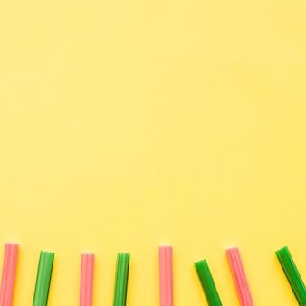 Linha de doces de alcaçuz vermelho e verde sobre fundo amarelo