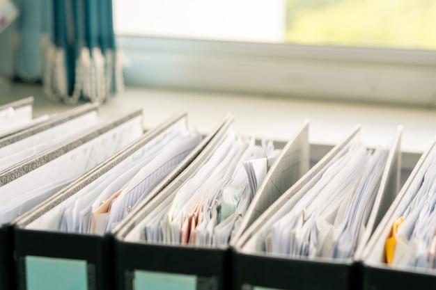 Linha de documentos em papel branco na pasta preta sobre a mesa de trabalho de escritório, arquivos de relatório