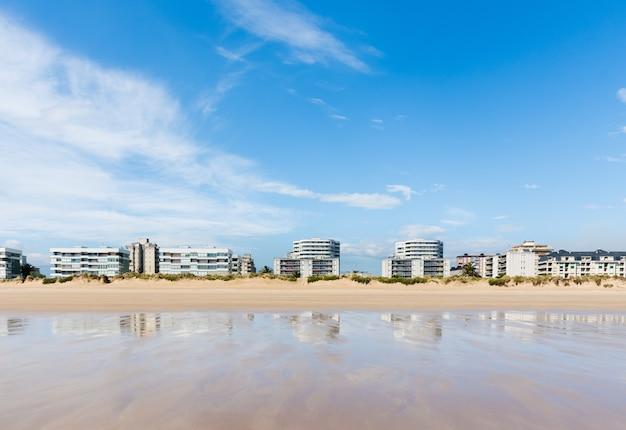 Linha de edifícios de frente para a praia de laredo. dia de sol e reflexo na areia molhada