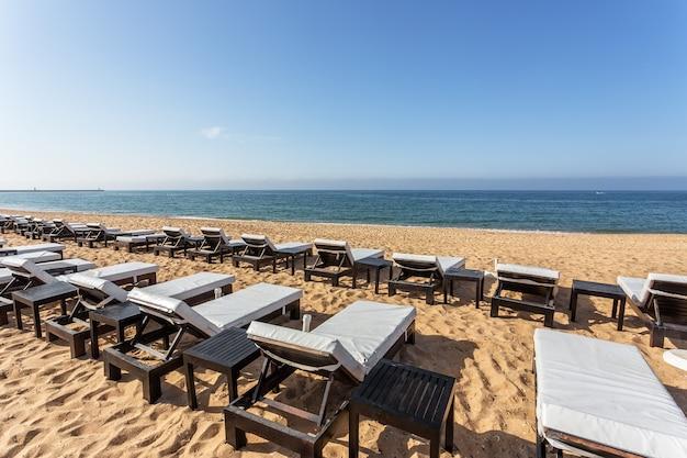 Linha de espreguiçadeiras para banhos de sol, close-up na praia no algarve.