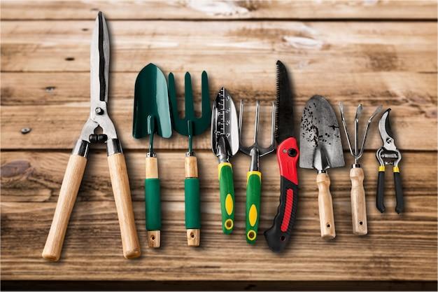 Linha de ferramentas de jardinagem em fundo de madeira