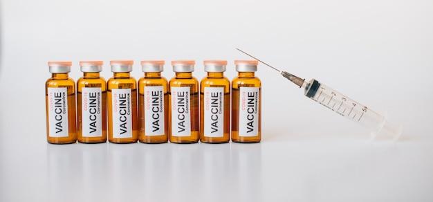 Linha de frascos de vacina contra coronavírus covid-19 e seringa médica com agulha