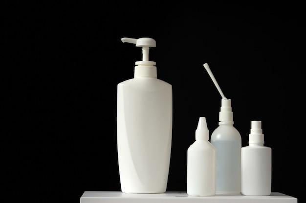 Linha de garrafas de desinfetantes para as mãos e sabonete líquido em fundo preto