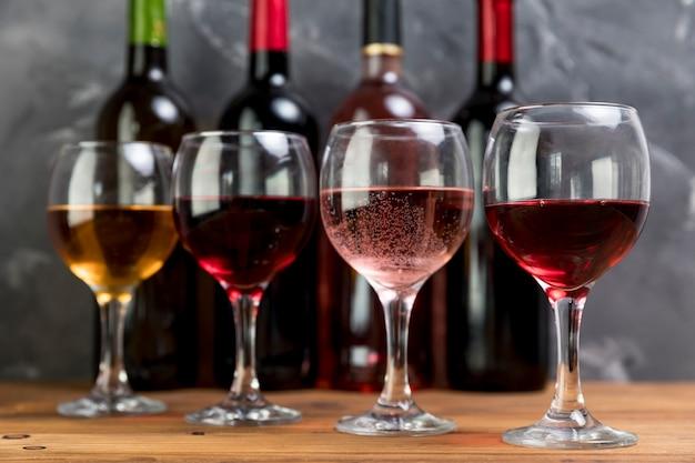 Linha de garrafas de vinho e taças de vinho