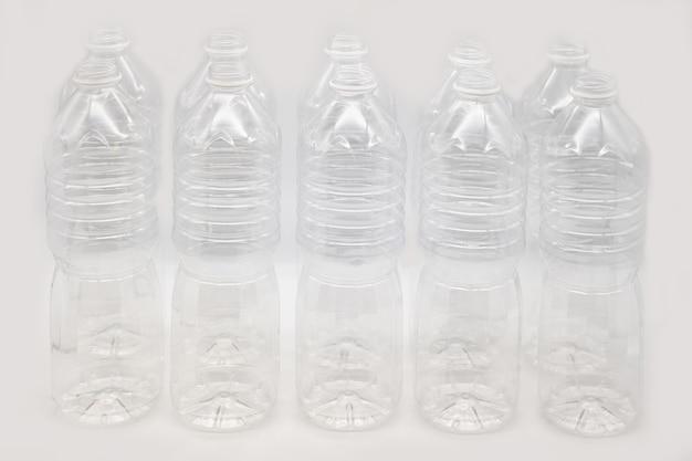 Linha de garrafas plásticas de água mineral isoladas em um fundo branco.
