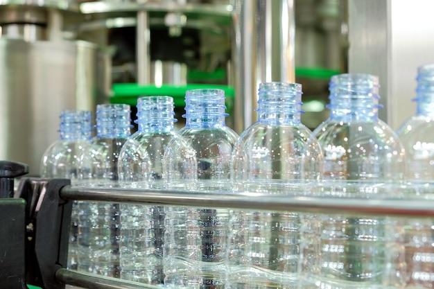 Linha de garrafas plásticas transparentes na esteira de máquinas,