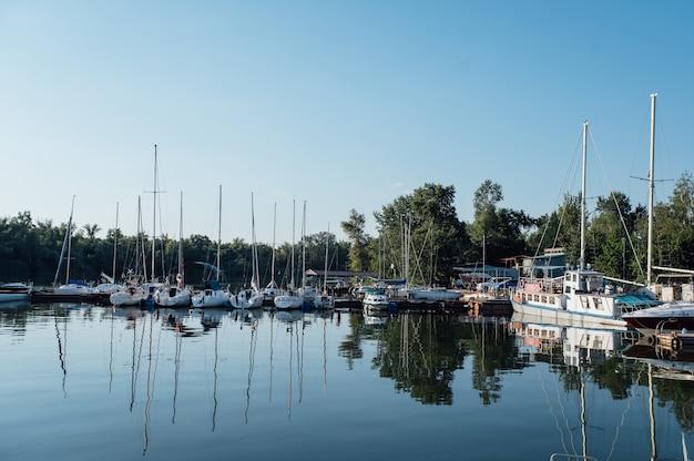 Linha de iates ancorados no porto de uma cidade europeia.