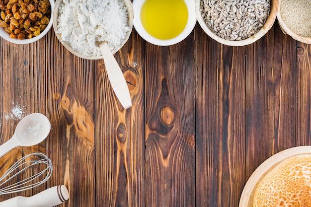 Linha de ingredientes de cozimento na mesa de madeira