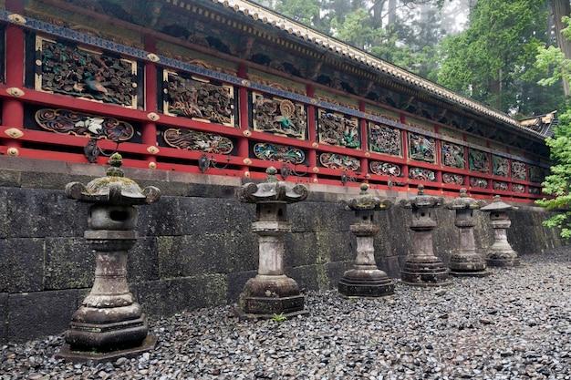 Linha de lanternas de pedra antigas perto da parede vermelha cênica do templo japonês