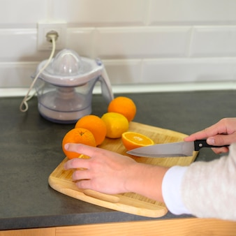 Linha de laranjas e faca na cozinha