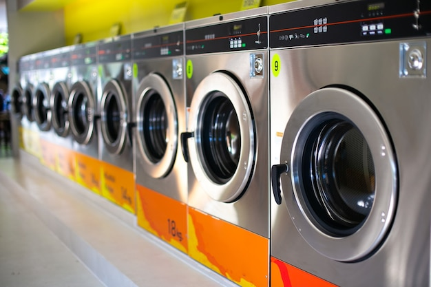 Linha de lavadoras industriais em lavanderia pública.