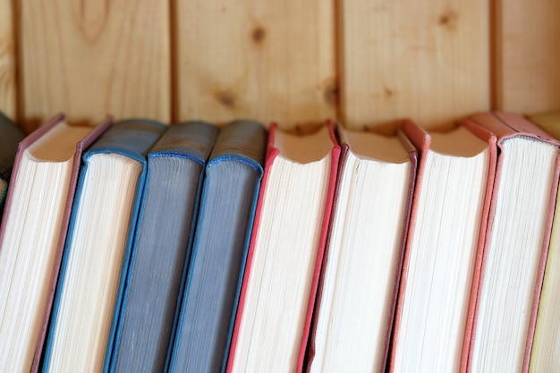 Linha de livros retrô em cores fortes, capas em pé na estante contra a parede de madeira marrom vista frontal.