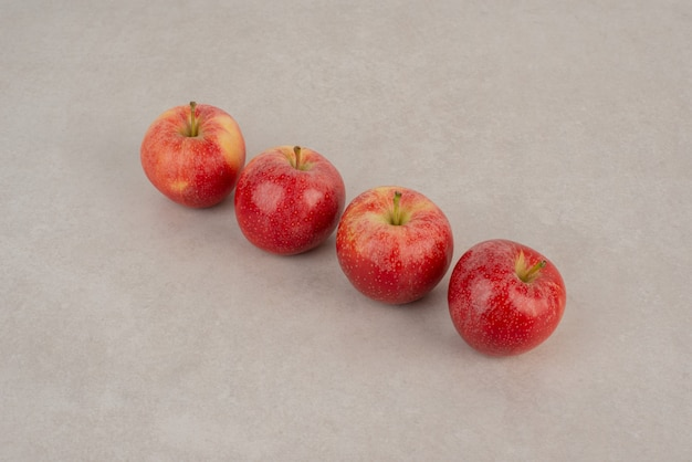 Linha de maçãs vermelhas em fundo branco.