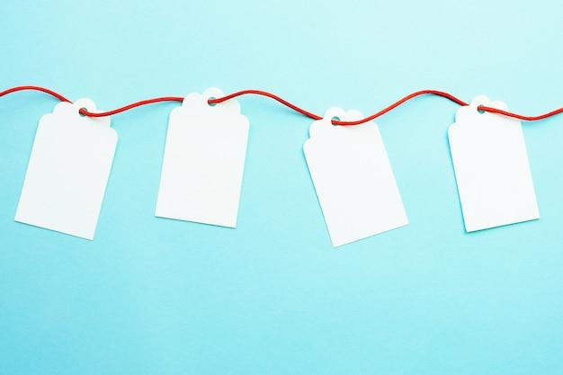 Linha de maquetes de etiquetas de presente em branco na fita vermelha no azul