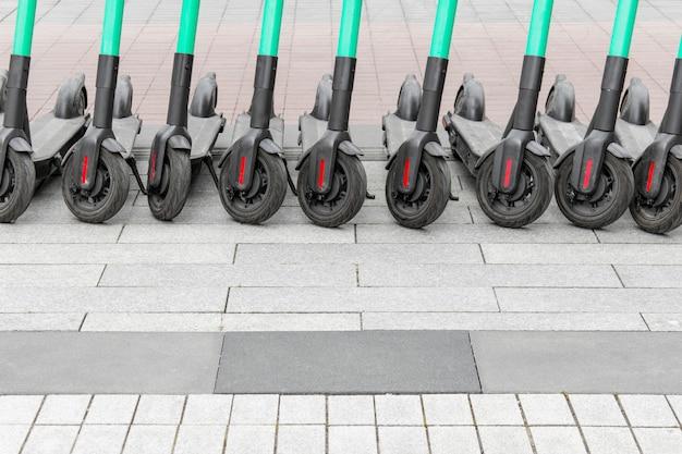Linha de muitas scooters elétricas em pé na calçada.