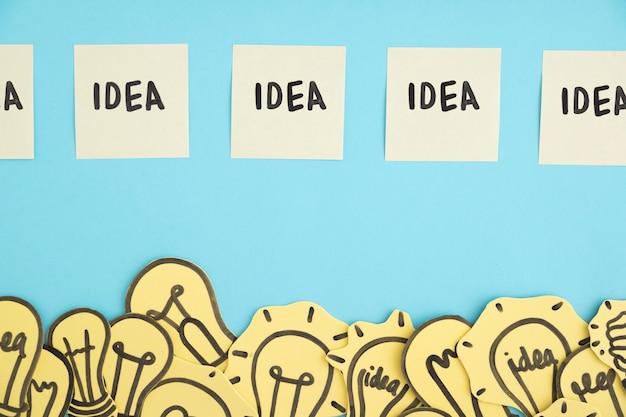 Linha de notas adesivas de ideia ao longo da fronteira de muitas lâmpadas contra o fundo azul