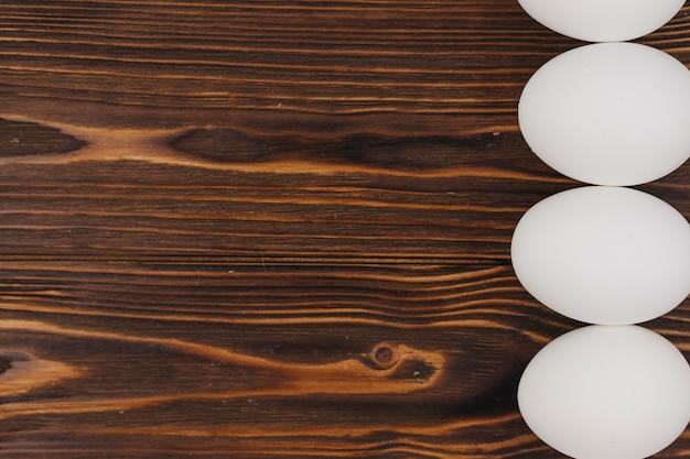 Linha de ovos brancos na mesa de madeira marrom