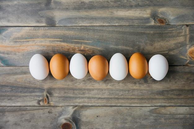 Linha de ovos marrons e brancos na prancha de madeira
