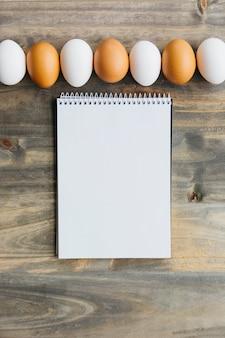 Linha de ovos marrons e brancos perto de bloco de notas em branco na mesa de madeira