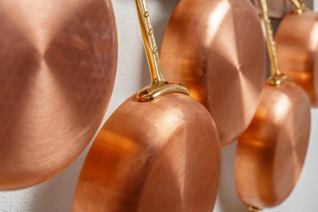 Linha de panelas de cobre limpas brilhantes, tamanho diferente, pendurado na prancha de madeira