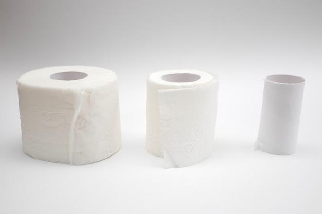 Linha de papel higiênico cheio e rolos de papel higiênico vazio em fundo branco.