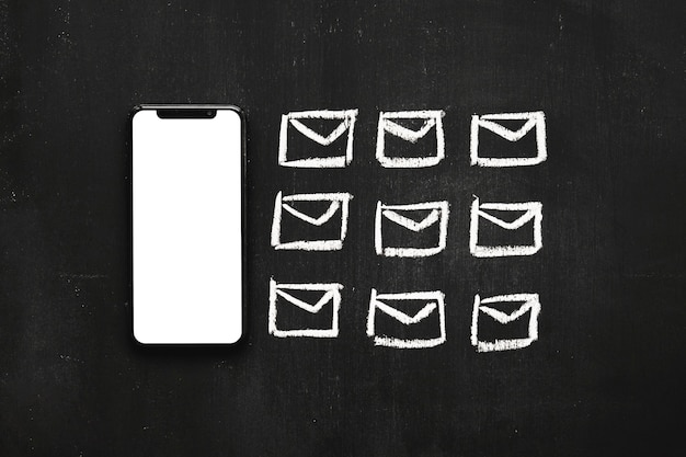 Linha de pequeno ícone de mensagens desenhadas perto do celular na lousa