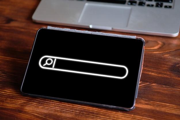 Linha de pesquisa com uma lupa em um tablet ao lado de um laptop em uma mesa de madeira. o conceito de busca de informações na internet.