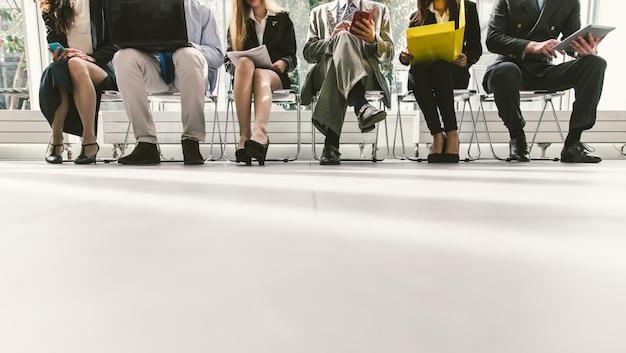Linha de pessoas de negócios, à espera de uma entrevista