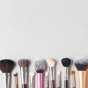 Linha de pincéis de maquiagem no fundo do pano de fundo branco