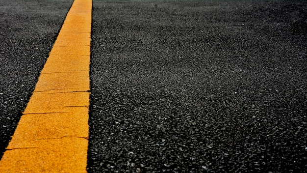 Linha de pintura amarela no asfalto preto. fundo de transporte espacial
