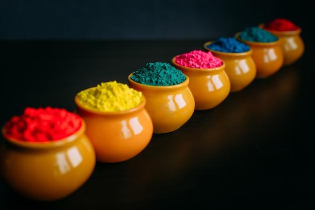 Linha de pó colorido de holi em copos closeup. cores brilhantes para o festival de holi indiano em panelas de barro. foco seletivo. fundo preto. cartão feliz holi