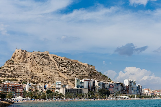 Linha de praia na cidade de alicante com o castelo de santa bárbara ao fundo.