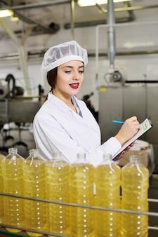 Linha de produção alimentar de óleo de girassol refinado. trabalhador de garota em uma fábrica em uma superfície de transporte com garrafas de óleo vegetal.