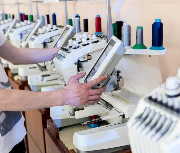 Linha de produção da indústria de tecidos. fábrica têxtil. pano de processo de alfaiataria de trabalho. máquina de bordar profissional. equipamento moderno