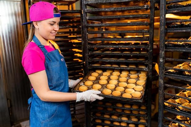 Linha de produção de biscoitos para assar. racks com pastelaria. mulher com bandeja na fábrica. fechar-se.