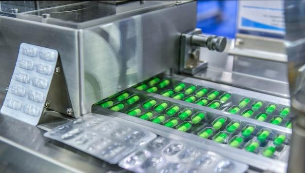 Linha de produção do comprimido do medicamento cápsula verde, conceito farmacêutico industrial.