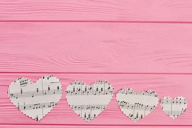 Linha de quatro corações de papel com notas musicais.