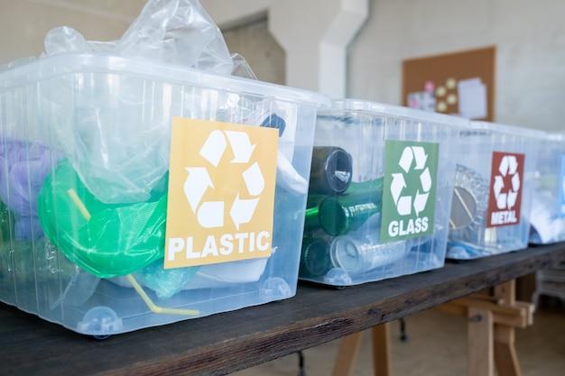 Linha de recipientes de plástico com doação reciclável na mesa preta