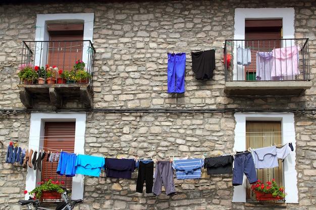 Linha de roupa pendurada em casas de parede de pedra