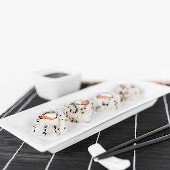 Linha de sushi na bandeja branca com pauzinhos