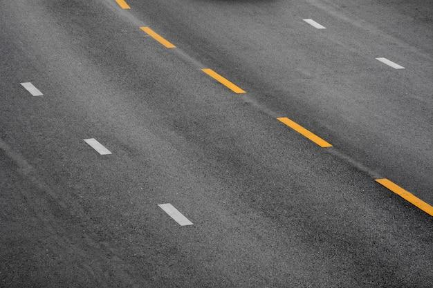 Linha de tinta amarela e branca no asfalto negro