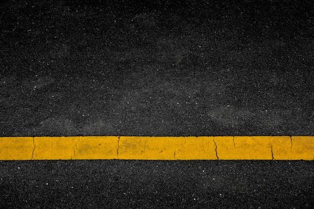 Linha de tinta amarela no asfalto negro
