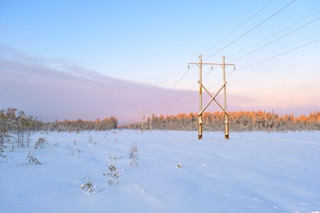 Linha de transmissão de energia em dia de inverno com neve. conceito de transporte de eletricidade