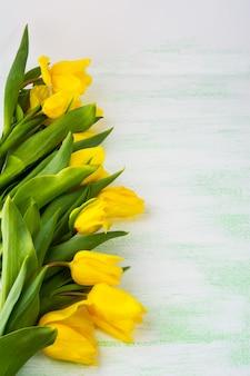 Linha de tulipas amarelas na superfície verde clara, vertical, cópia espaço