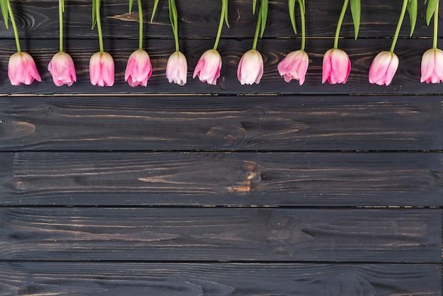 Linha de tulipas cor de rosa em fundo de madeira rústica