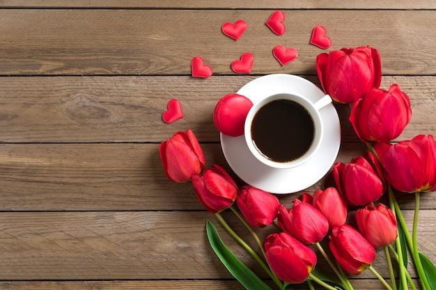 Linha de tulipas vermelhas e xícara de café preto americano em fundo de madeira dia das mães